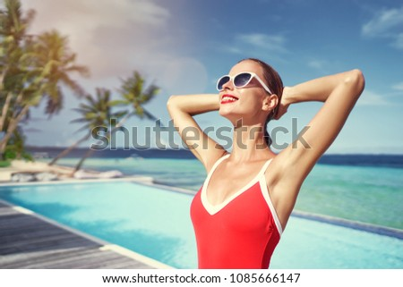 Summer vacation and fashion. Beautiful young woman in red swimsuit near swimming pool on tropical beach. #1085666147
