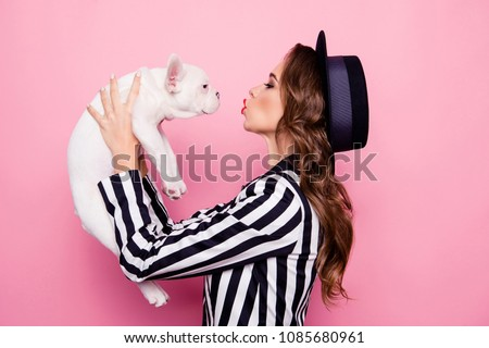 Side view, half face, profile portrait of attractive, pretty, charming girl raise dog in front of face, blowing kiss to pet, isolated on pink background