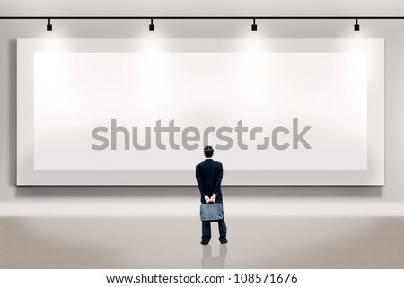 Shot of businessman looking at large empty billboard. Copy space available  for your own work