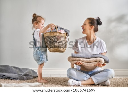 Beautiful young woman and child girl little helper are having fun and smiling while doing laundry at home. #1085741699