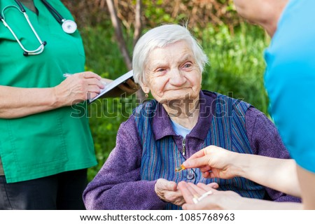 Elderly ill woman receiving pills from nurse outdoor, doctor writing medical prescription in the background #1085768963