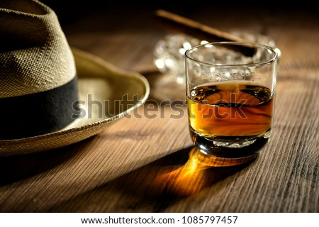 glas of rum, cigar and a panama hat in a bar in Cuba #1085797457