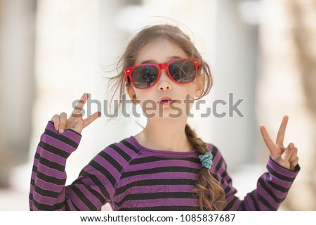 A little girl of 6 years in sunglasses is happy and gesticulates with her hands and fingers #1085837687