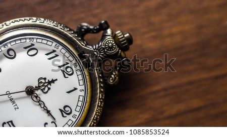 old vintage pocket watch showing time on wooden background #1085853524