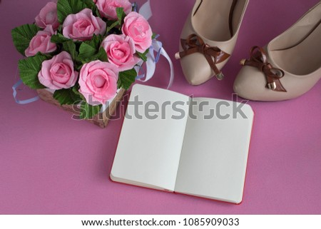 Women's shoes, notebook and a bouquet of roses on a pink background. Flat lay. Top view. #1085909033