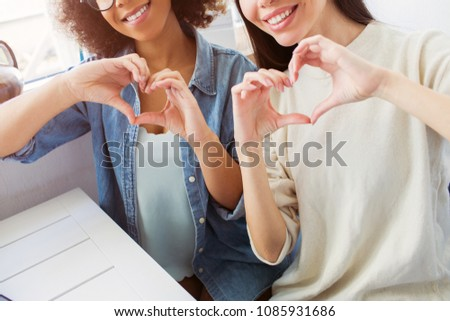 Close up of two young women sitting at the table. They are making heart from their fingers. Girls are happy and cheerful. #1085931686