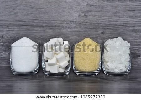 Cube sugar, raw sugar , crystalline sugar and granulation sugar in clear glasses with grey wooden background #1085972330