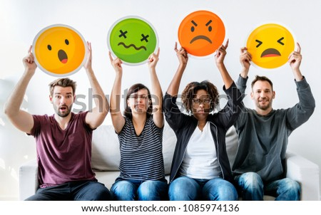 Diverse people holding emoticon #1085974136