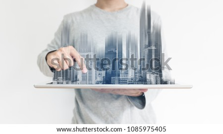 a man using digital tablet, and modern buildings hologram. Real estate business and building technology concept #1085975405