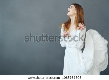 joyful woman in white dress dancing                               #1085981303