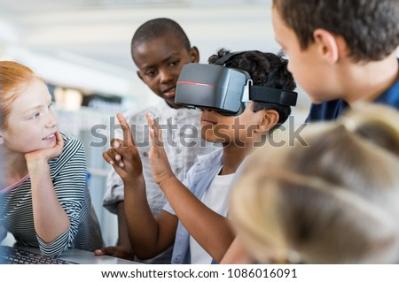 Mixed race child with vr virtual reality goggles in classroom. Multiethnic pupil having fun with virtual reality headset at elementary school. Happy boy gesturing while using VR headset in classroom. #1086016091