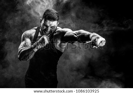 Sport concept. Sportsman muay thai boxer fighting on black background with smoke. Royalty-Free Stock Photo #1086103925