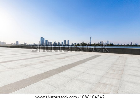 Panoramic skyline and buildings with empty concrete square floor #1086104342
