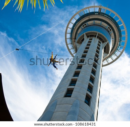 Auckland Sky Tower from below with blue sky and someone jumping off #108618431
