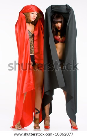 Photo of two sexual, naked girls in red and black cloaks. Standing. #10862077