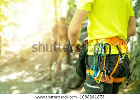Detail of young man who preparing on a climb and standing a next to rock wall. Equipment for climbing on a man with copy space for a text.  #1086241673