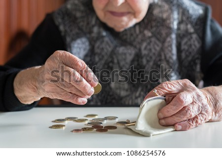 Elderly 95 years old woman sitting miserably at the table at home and counting remaining coins from the pension in her wallet after paying the bills. #1086254576