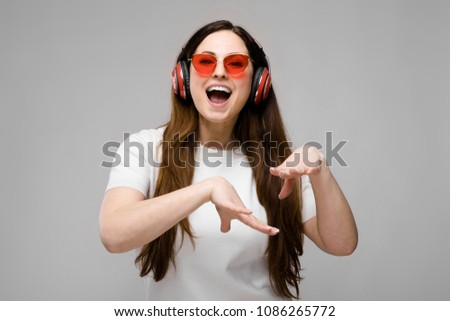 Portrait of emotional beautiful happy plus size model in headphones and sunglasses standing in studio looking in camera listening to music #1086265772