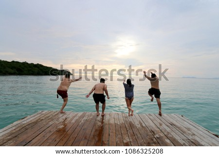 Multiracial group of happy young people, family, friends jumping from wooden the bridge to the sea with beautiful blue sky in summer near the beach.Happiness, success,friendship and community concept #1086325208