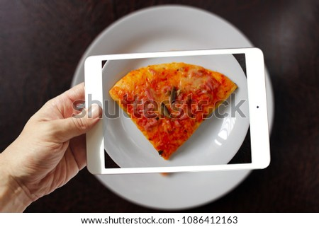 male hand holding tablet take photo of slice of pizza on table