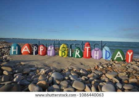 Happy Birthday with multicolored stones on the beach  #1086440063