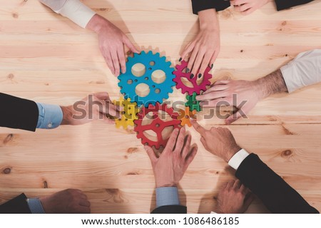 Business team connect pieces of gears. Teamwork, partnership and integration concept #1086486185