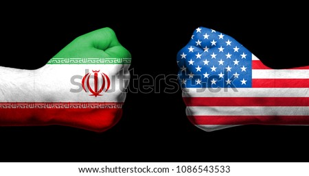 Flags of USA and Iran painted on two clenched fists facing each other on black background/Tensed relationship between USA and Iran concept #1086543533