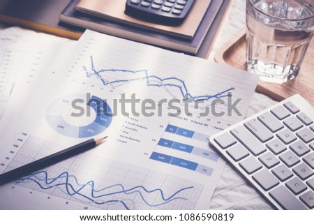 Blue chart graph data analysis documents, pencil, modern keybord, glass of water, calculator, notebooks on bed. Morning daylight in bedroom, vintage retro style. Freelance job work at home concept. #1086590819
