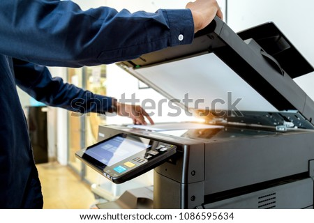 Bussiness man Hand press button on panel of printer, printer scanner laser office copy machine supplies start concept. #1086595634