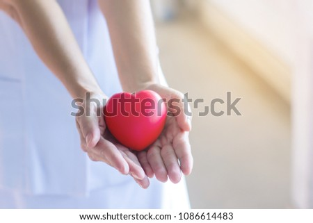 Closeup Nurse hands holding and giving red heart in hospital.healthy and healthcare concept with selective focus. #1086614483