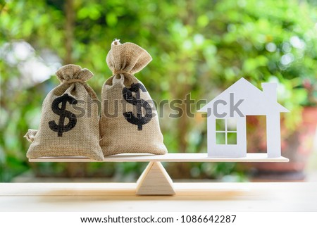 Home loan / reverse mortgage or transforming assets into cash concept : House paper model , US dollar hessian bags on a wood balance scale, depicts a homeowner or a borrower turns properties into cash #1086642287