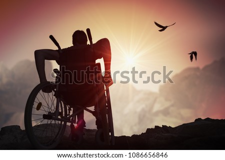 Disabled handicapped man has a hope. He is sitting on wheelchair and stretching hands at sunset. #1086656846