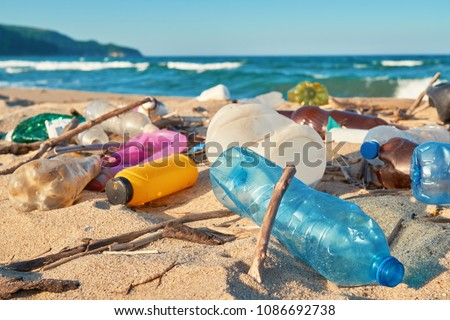 Spilled garbage on the beach of the big city. Empty used dirty plastic bottles. Dirty sea sandy shore the Black Sea. Environmental pollution. Ecological problem. Bokeh moving waves in the background   #1086692738