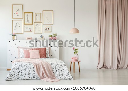 Pink blanket on bed with patterned headboard in feminine bedroom interior with gallery of posters #1086704060