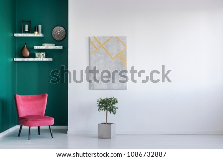 Minimalist interior in white and green with red armchair, a plant, painting on the wall and shelves with a clock #1086732887