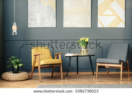 Retro chairs in vintage living room interior with paintings, lamp, plant and book on the table #1086738023