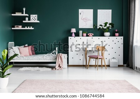 Posters on green wall in girl's bedroom interior with white bed and wooden pink chair at dressing table #1086744584