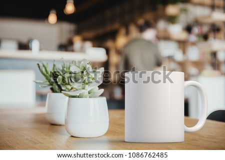 White coffee Mug Mockup set-up in a cafe, next to cactus plants and with blurred background. Great for overlaying your custom quotes and designs for selling mugs. #1086762485