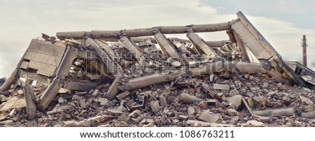 Industrial concrete building destructed by strike. Disaster scene full of debris, dust and crashed buildings. #1086763211