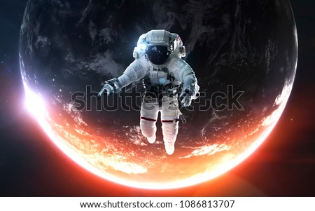 Astronaut at the spacewalk. Awesome beautiful Earth planet in cold and warm light. Elements of this image furnished by NASA Royalty-Free Stock Photo #1086813707