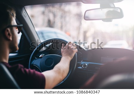 young man driving a business car. trip of a businessman in sunny weather. #1086840347
