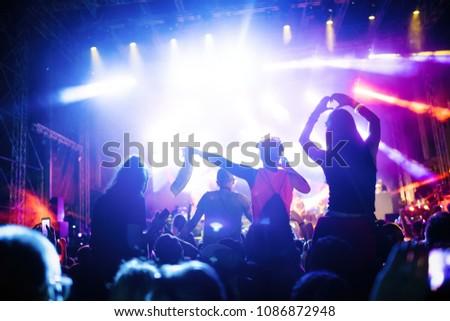 Portrait of happy crowd enjoying at music festival #1086872948