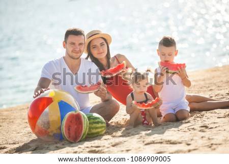 Cheerful family on the beach. Family on vacation #1086909005