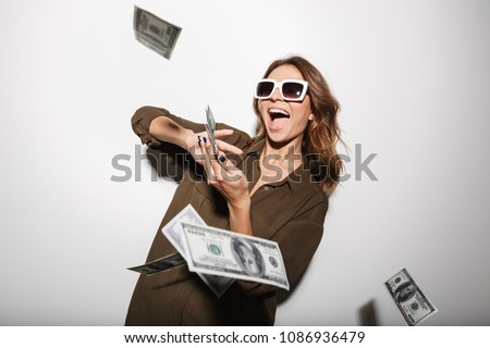 Portrait of a happy young woman in sunglasses throwing out money banknotes isolated over white background