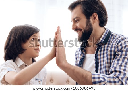 Happy father and son give five to each other. Happy relationship between parent and kid. #1086986495