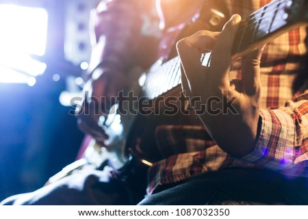Men play electric guitar on stage hand close-up #1087032350