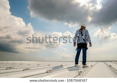 Construction engineer wear safety uniform inspection metal roofing work for roof industrial concept with copy space #1087068587
