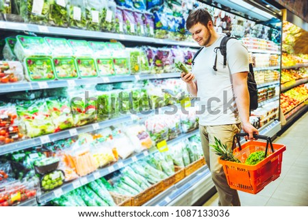 young smiling man choosing products in grocery store. shopping concept. lifestyle #1087133036