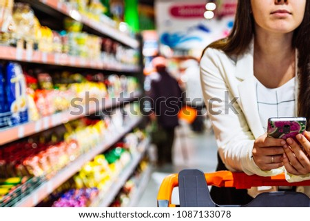 woman with smartphone in store. grocery shopping. gadgets and shopping. #1087133078