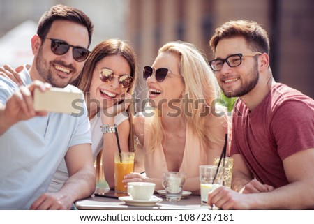 Friends having a great time in cafe.Friends smiling and sitting in a coffee shop, drinking coffee and enjoying together. #1087237181
